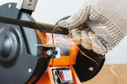 Gloved hand sharpening a mower blade on grinder