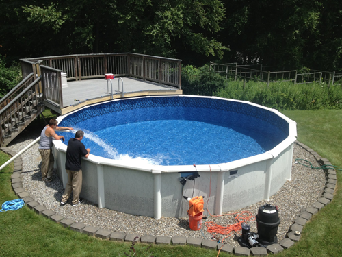 Above ground pool with a rock landscaping being filled with water by two men