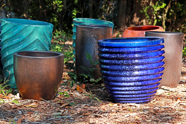A variety of colorful ceramic planters sitting on the ground