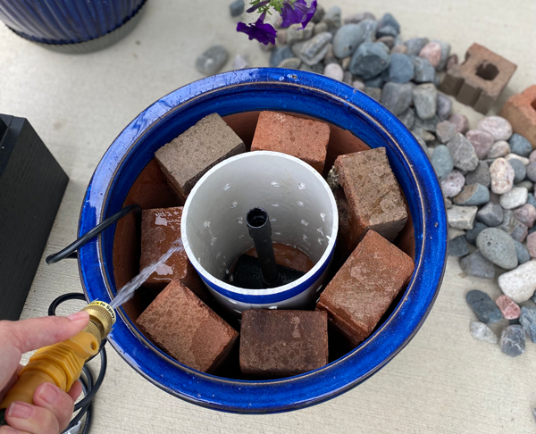 Planter assembled with water pump, pvc riser, and filler bricks around perimeter